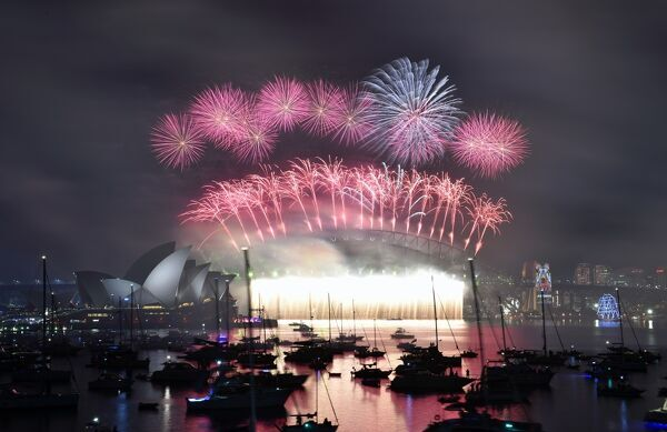 Fireworks light up the sky over Sydney's Opera House (L) and Harbour Bridge during New Year celebrations in Sydney on January 1, 2016. / AFP PHOTO / SAEED KHAN