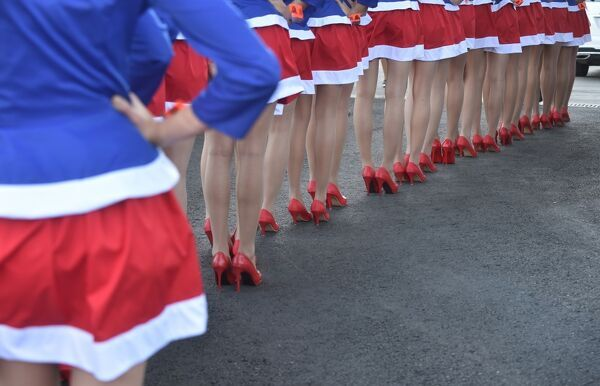 Pit lane girls line up during the qualifying session of the inaugural Russian Grand Prix at the Sochi Autodrom in Sochi on October 11, 2014. AFP PHOTO / DIMITAR DILKOFF / AFP PHOTO / DIMITAR DILKOFF