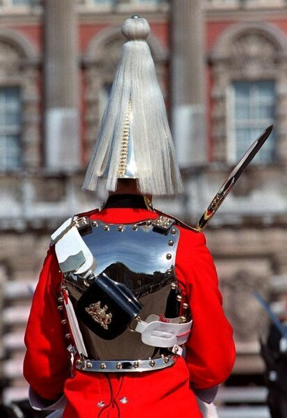 A shining example of the British monarch's horseguards regiment, uniformed in the traditional pyramid-fringed ceremonial helmet and highly-polish breast-plate, stands on parade in Whitehall 07 April while reflecting the customary admiration