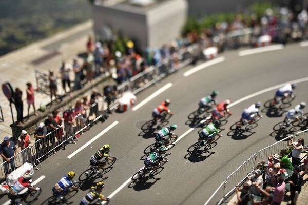 A photo taken with a tilt and shift lens shows the pack riding along the harbour of Concarneau, western France, during the fifth stage of the 105th edition of the Tour de France cycling race between Lorient and Quimper, western France, on July 11, 2018