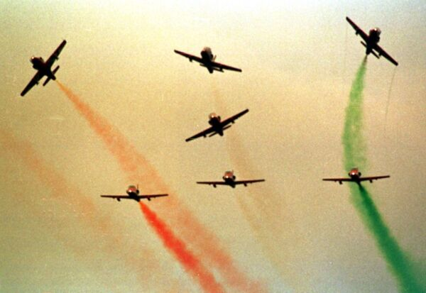 A wave of seven locally-built military planes stream a plume of coloured smoke at the beginning of India's largest airshow AERO India '98 08 December in Bangalore. More than 100 aeronautical firms from 17 countries are at the five-day event