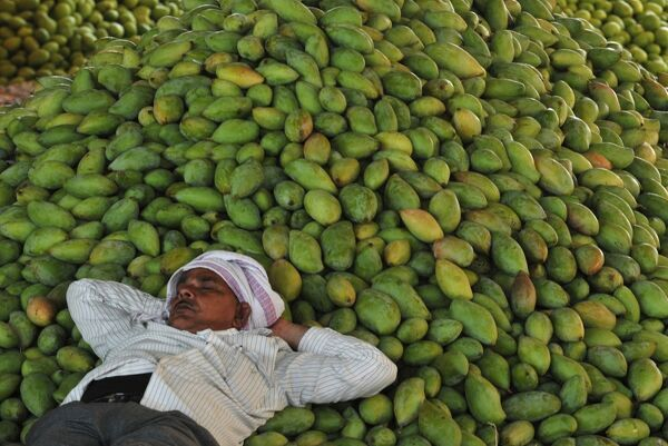 An Indian labourer sleeps as he waits for mangoes to be auctioned at the Gaddiannaram Fruit Market on the outskirts of Hyderabad on April 6, 2016