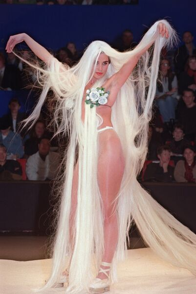 Wearing a wig, a model presents a bathing suit during French designer Jean-Paul Gaultier's Spring-Summer 1992 ready-to-wear collection, 16 October 1992, in Paris. Jean-Paul Gaultier will celebrate his 30-years Fashion career in October 2006