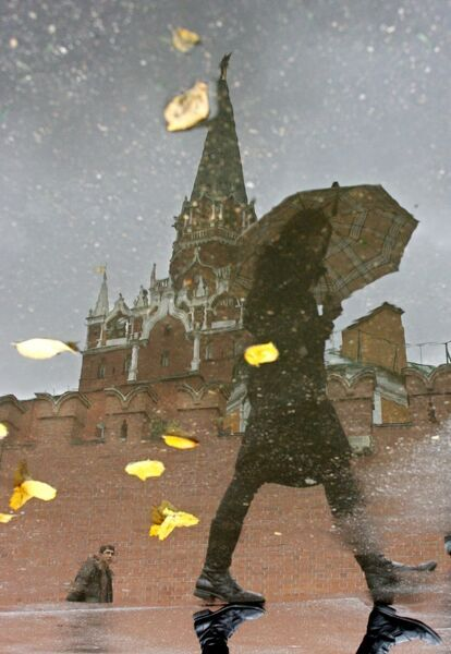 The Kremlin tower and passing woman are reflected in a puddle during rainy autumn weather in Moscow, 12 October 2006. AFP / AFP PHOTO / STR
