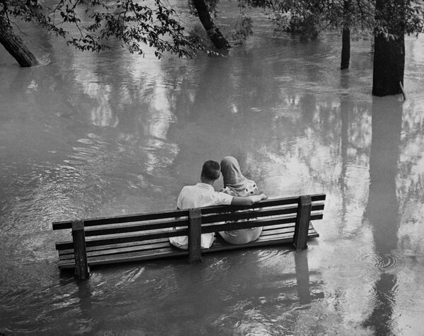 A picture taken 27 August 1960 of a young American couple on a bench with their feet in the water of the Bronx River near New York because of torrential downpours in the last few days. AFP PHOTO
