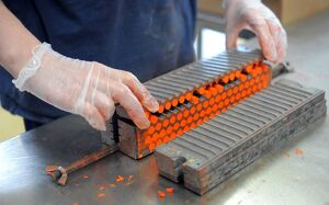 An employee makes pastels in a workshop at the Raphael-Isabey-Sennelier factory in