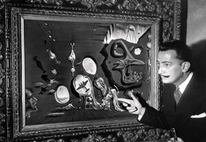 Salvador Dali poses in front of one his paintings