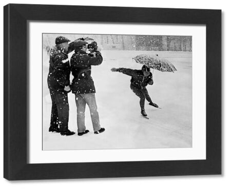 An unidentified woman speed skater, holding an umbrella to protect herself from falling snow, skates past a cameraman during practice, 06 February 1968 in Grenoble (French Alps) at the Winter Olympic Games. / AFP PHOTO / STAFF