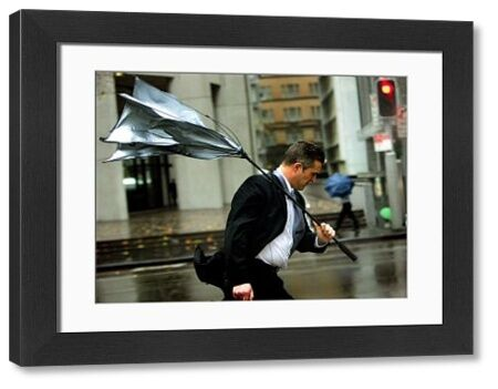 A man's umbrella turns inside-out as he battles strong winds and rain in Sydney, 30 June 2005
