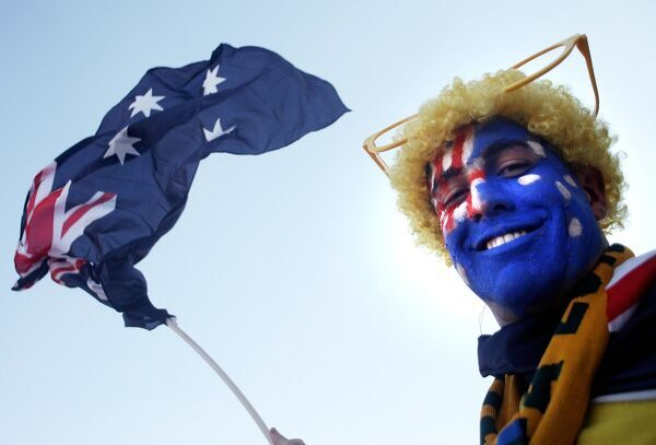 An Australian football team supporter poses with the country's flag. AFP PHOTO / PABALLO THEKISO / AFP PHOTO / PABALLO THEKISO