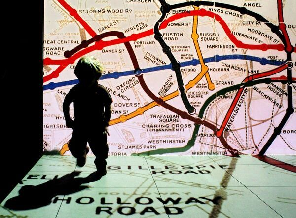 A young visitor to the newly refurbished London Transport Museum runs in front of a projection of an old British underground train map in central London, 22 November 2007. Redevelopment includes three new galleries, improvements to the roof and infrastructure