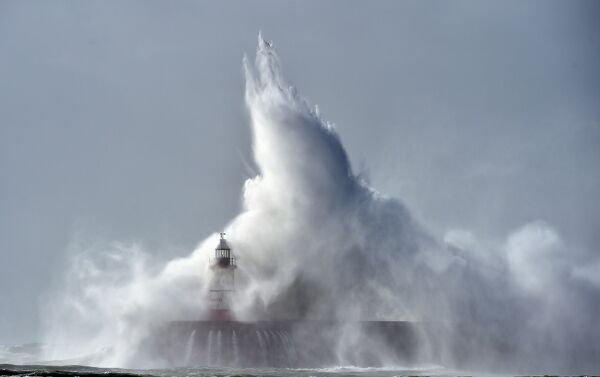 Waves crash over Newhaven Lighthouse on the south coast of England on October 21, 2017 as Storm Brian hits the country. / AFP PHOTO / GLYN KIRK