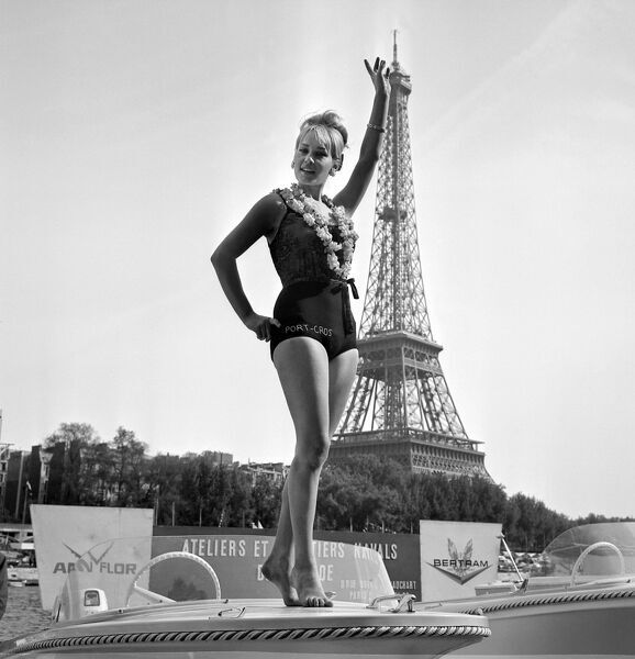 French Arlette Paganelli, 20, standing of a boat roof, waves 22 May 1965 in front of Eiffel Tower on next to Seine river in Paris after being elected the Queen of the Boat Show 1965. AFP PHOTO / AFP PHOTO