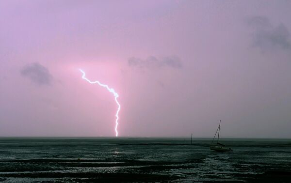 A lightning strike hits the ground above the Arcachon basin during a storm at sunset on May 5, 2017. / AFP PHOTO / NICOLAS TUCAT