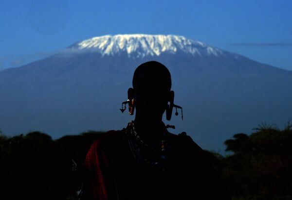 A Maasai man is silhouetted in front of Mount Kilimanjaro in Kimani on December 13, 2014
