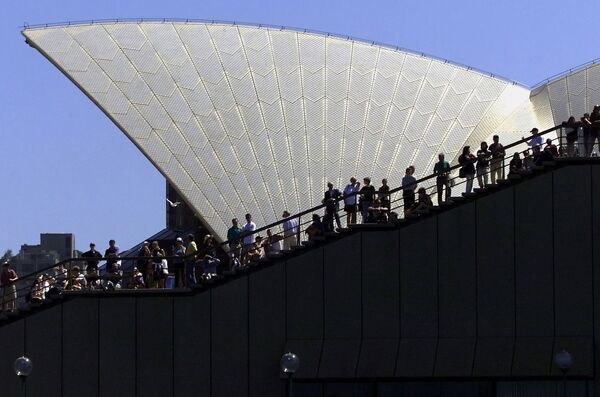 Spectators line the stairs at the Sydney Opera House to watch the final sailing race in the soling class between Denmark and Germany 30 September at the Olympic Games. AFP PHOTO/SVEN NACKSTRAND / AFP PHOTO / SVEN NACKSTRAND