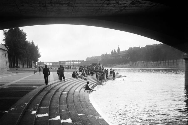People bathe in the Seine river near the Pont d'Ina, in July 1945 in Paris, during a heat wave in the 1945 summer. In the background, the Pont de Bir-Hakeim. (Photo by - / AFP)