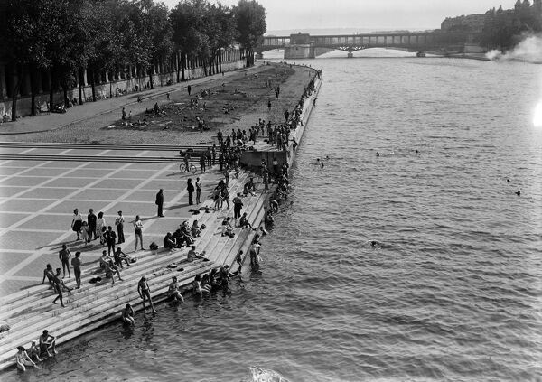 People bathe in the Seine river near the Pont d'Ina, in June 1946 in Paris, during a heat wave at the beginning of the 1946 summer. In the background, the Pont de Bir-Hakeim. (Photo by - / AFP)