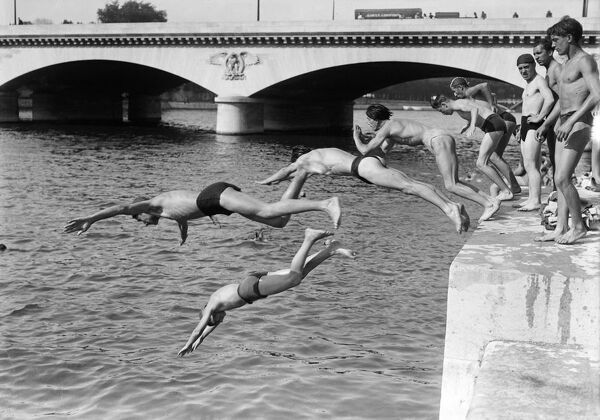 People dive in the Seine river near the Pont d'Ina, in June 1946 in Paris, during a heat wave at the beginning of the 1946 summer. (Photo by - / AFP)