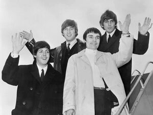 Beatles salute as they leave London, June 1964