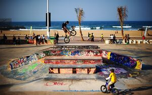 A BMX (Bicycle Motor Cross) rider performs on a ramp in a skatepark decorated with
