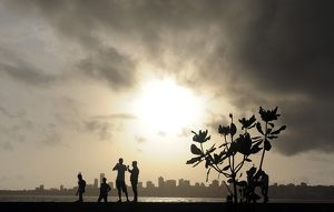 TOPSHOTS Indians stroll near the seafront as dark clouds gather over city skyline