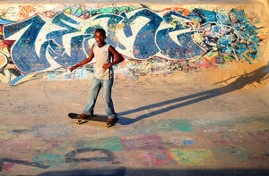 sport/skate/young boy skateboards past ramp decorated graffiti