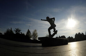 sport/skate/youth performs trick skateboard warm autumn sunny